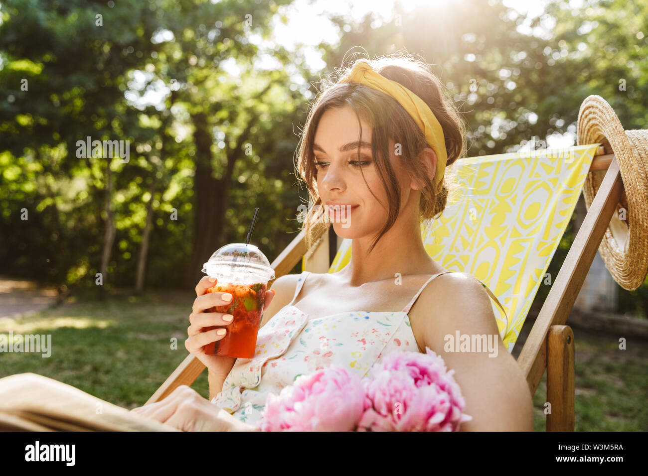 Image of a beautiful young amazing woman in green park drinking juice lies on sun bed reading book. - Stock Image