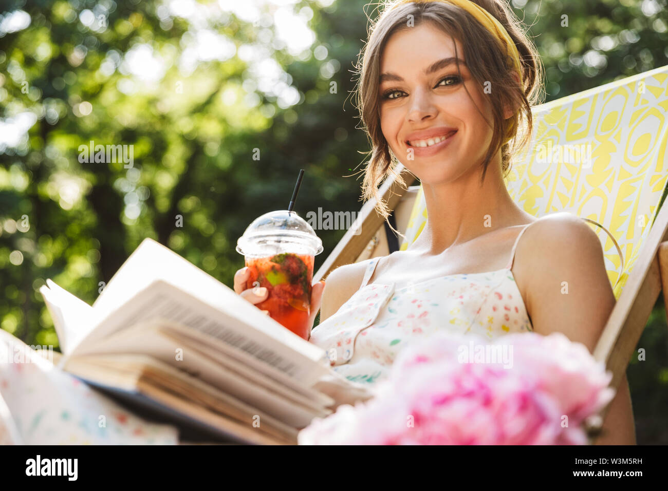 Image of a cheery smiling beautiful young pretty woman in green park drinking juice lies on sun bed reading book. - Stock Image