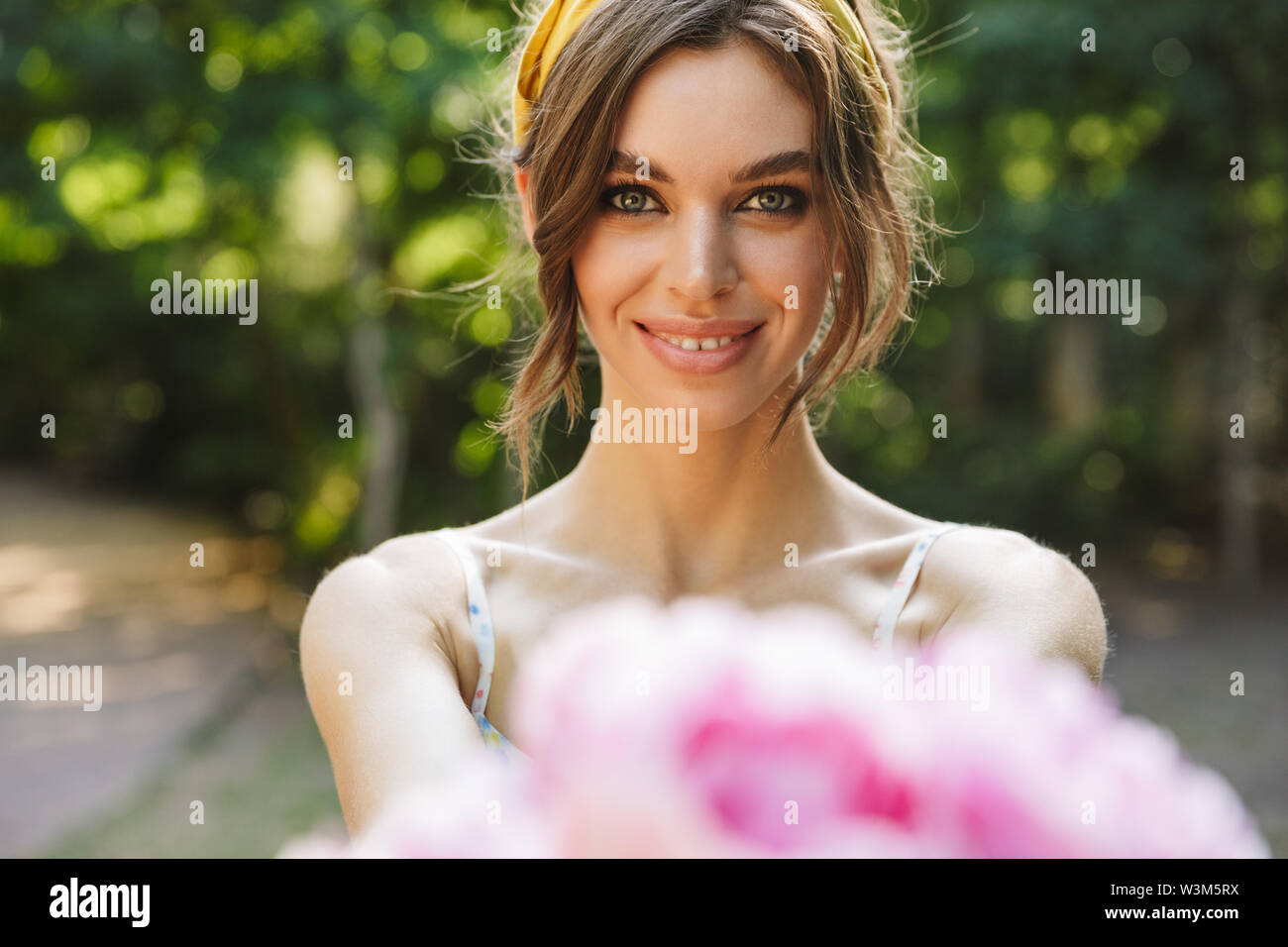 Image of a cheery happy positive beautiful young pretty woman in green park give you pink flowers. - Stock Image