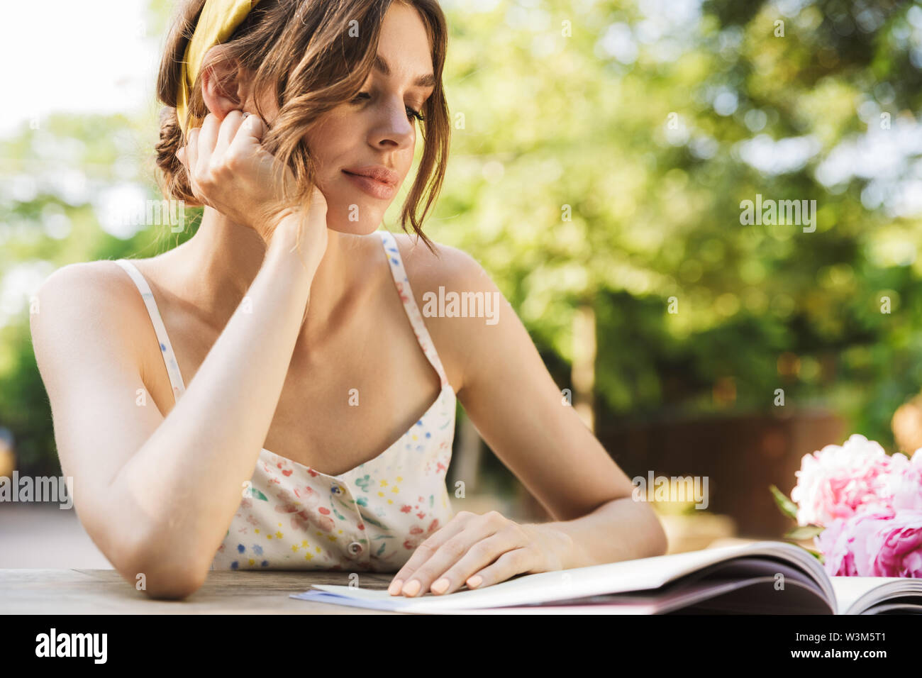 Photo of a beautiful concentrated young pretty woman sitting at the table in green park reading magazine. - Stock Image