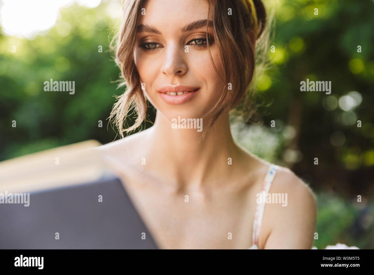 Photo of concentrated pretty beautiful young woman in green park reading book. - Stock Image
