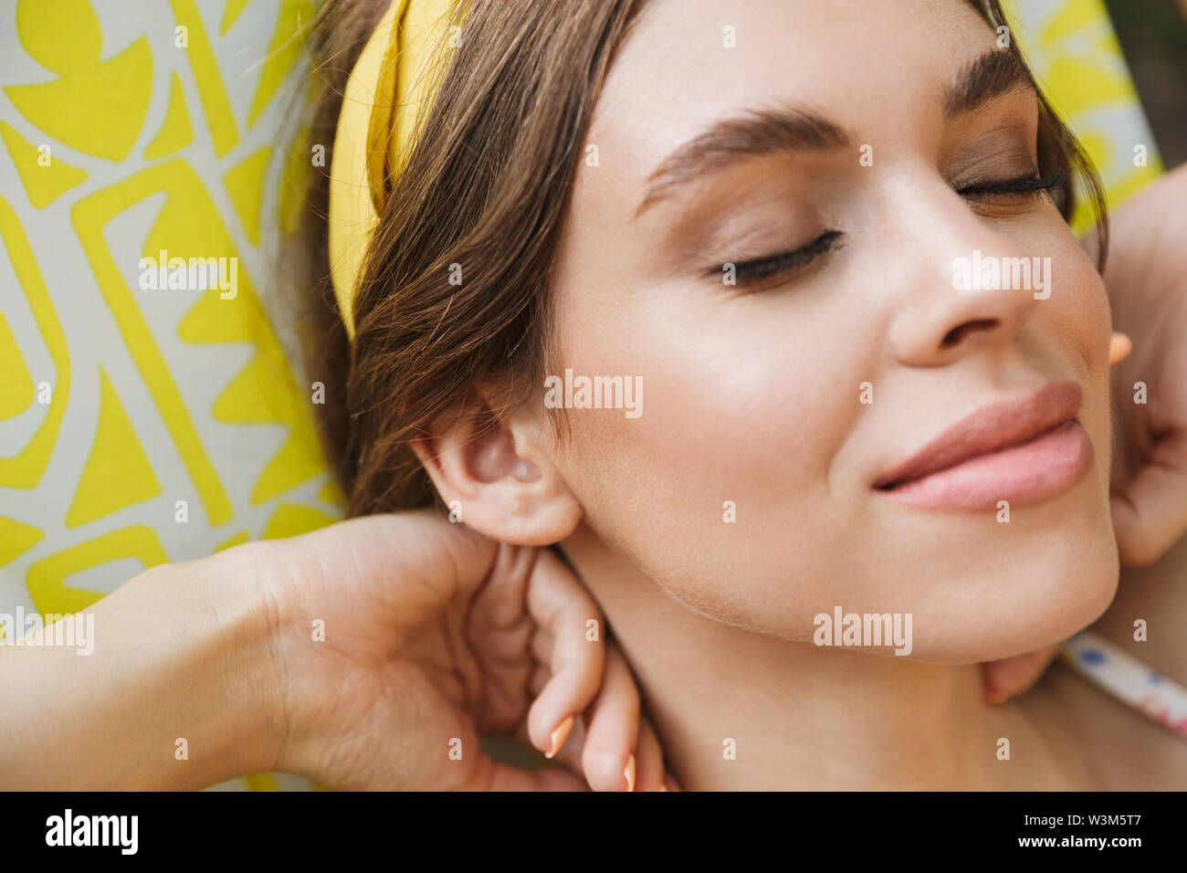 Image of a pleased beautiful young pretty woman in green park lies on sun bed. - Stock Image
