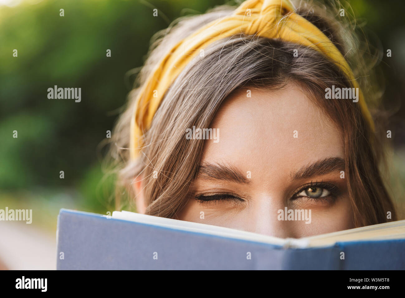 Photo of cute positive pretty beautiful young woman in green park reading book covering face winking. - Stock Image
