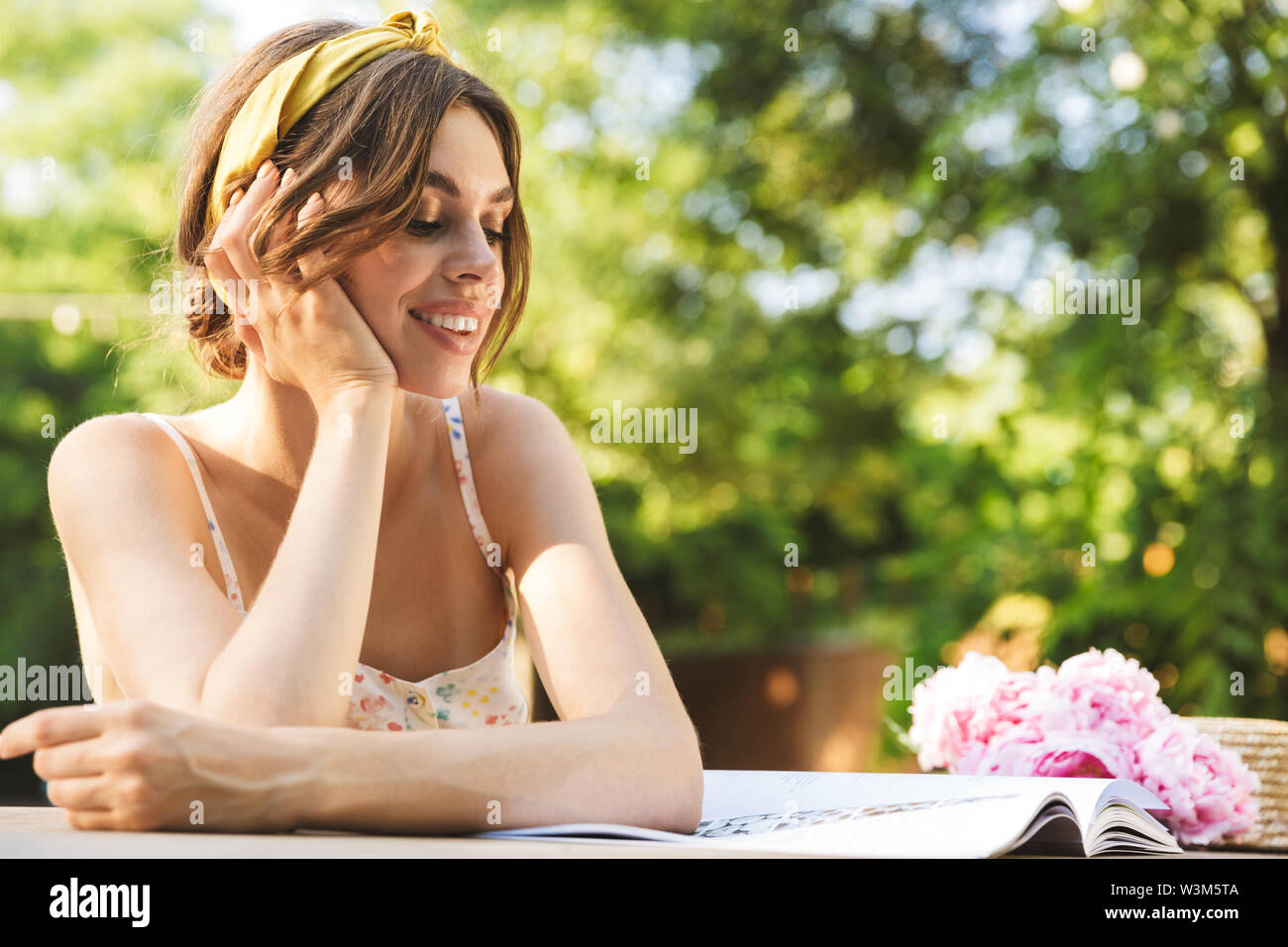 Photo of a beautiful positive young pretty woman sitting at the table in green park reading magazine. - Stock Image
