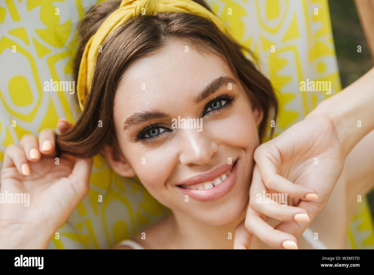 Image of a cheerful happy beautiful young pretty woman in green park lies on sun bed. - Stock Image