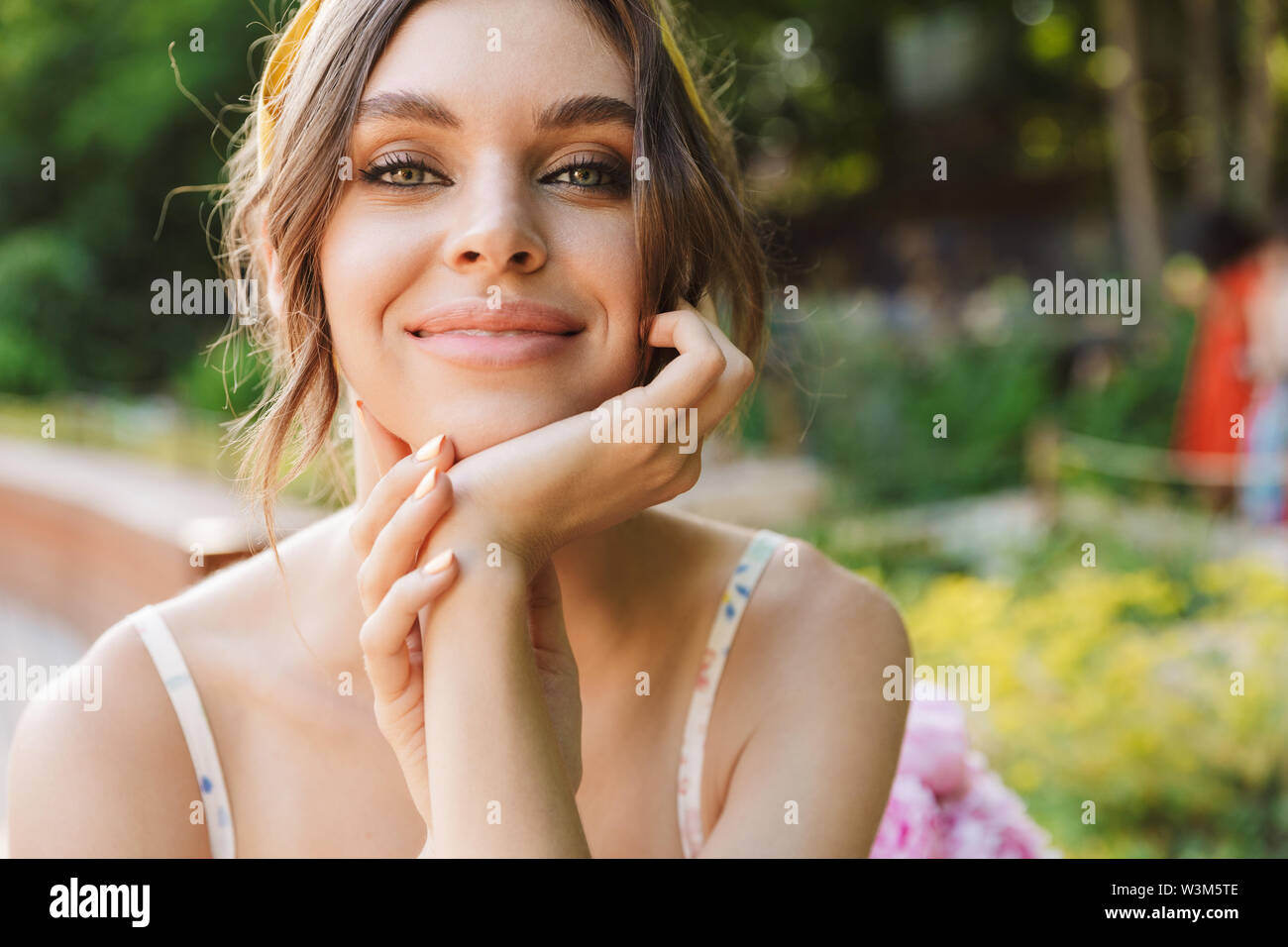 Photo of a smiling optimistic beautiful young pretty woman in green park looking camera. - Stock Image