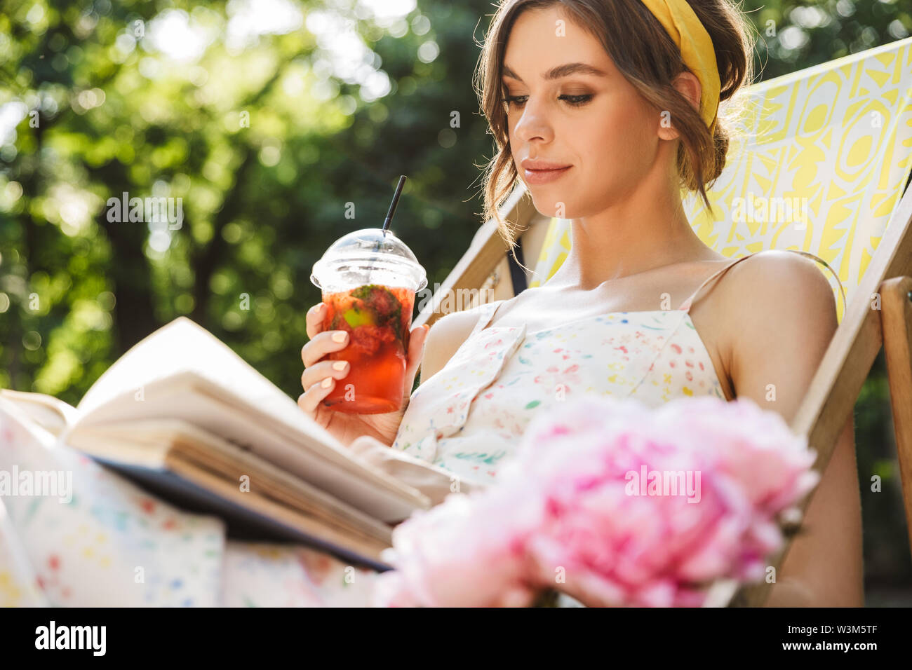 Image of a concentrated beautiful young pretty woman in green park drinking juice lies on sun bed reading book. - Stock Image