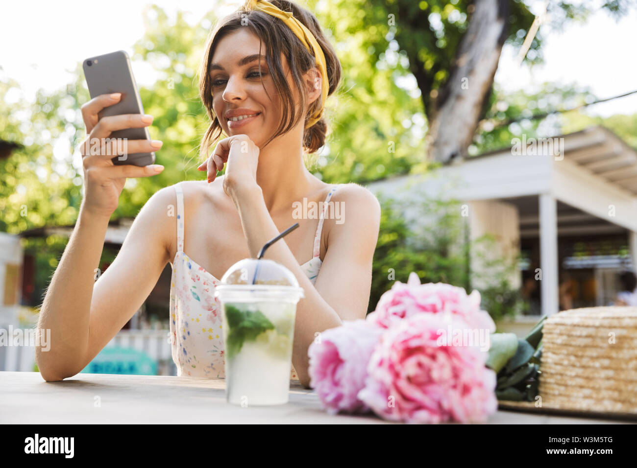 Image of a beautiful happy young amazing woman sitting at the table with flowers in green park using mobile phone. - Stock Image