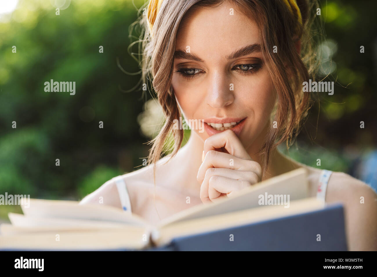 Photo of serious amazing pretty beautiful young woman in green park reading book. - Stock Image