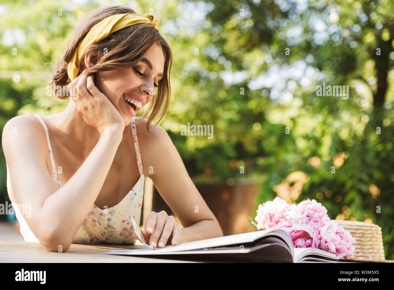 Photo of a beautiful pleased happy young pretty woman sitting at the table in green park reading magazine. - Stock Image