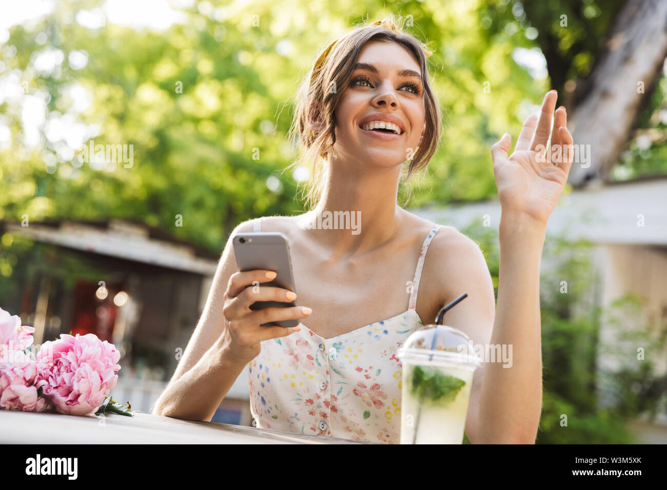 Image of a beautiful cheery smiling young amazing woman sitting at the table with flowers in green park using mobile phone waving to friend. - Stock Image