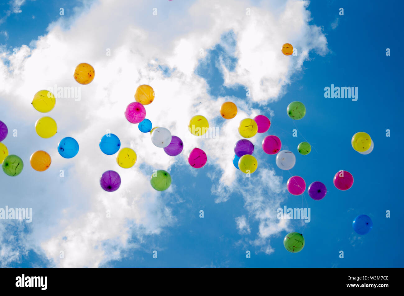 Colourful balloons in the blue cloudy sky - Stock Image