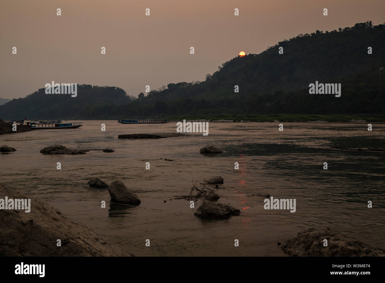 View of few river cruise ships on the Mekong River and Chomphet District across the river in Luang Prabang, Laos, at sunset. Stock Photo