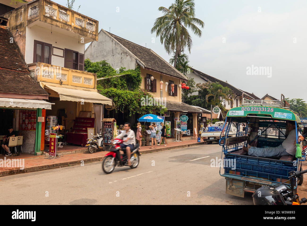 Few tourists and little traffic on the Sisavangvong Road in Luang Prabang, Laos, on a sunny day. Stock Photo