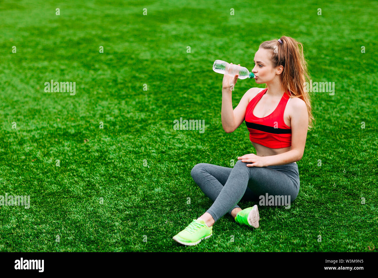Beautiful Smiling Woman Relaxing on the Grass in the Park During Training. Sport and Fitness Concept. - Stock Image