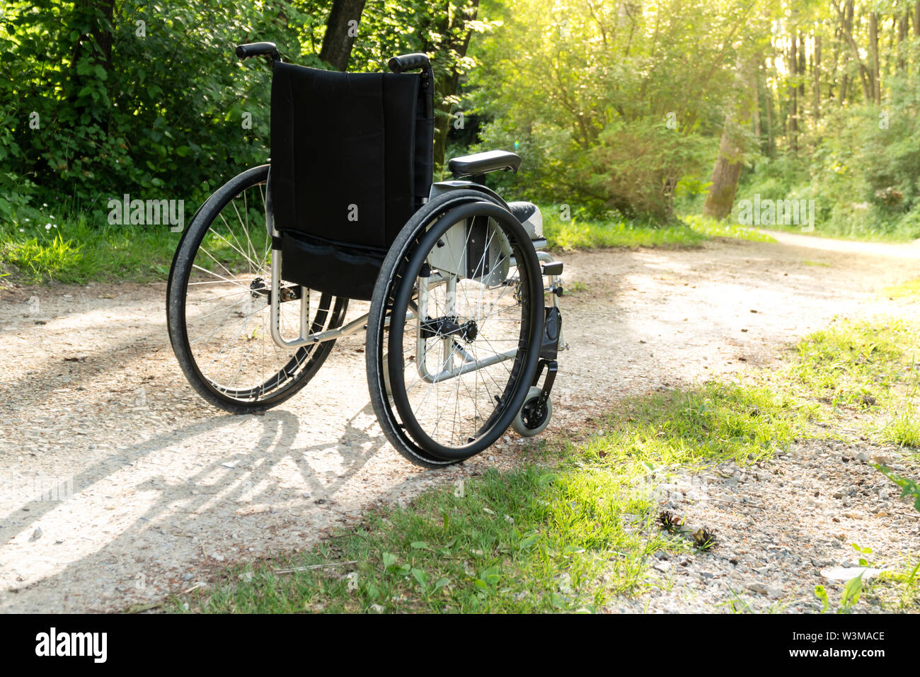 Empty wheelchair parked in park, health care concept, with sun flare Stock Photo