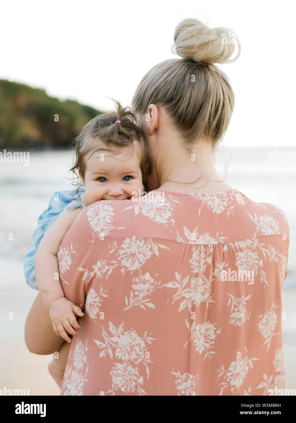 Woman holding baby daughter on beach Stock Photo