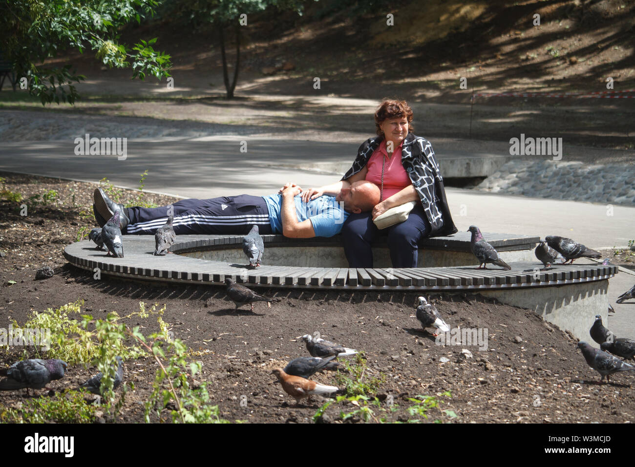 Kharkiv, Ukraine - June 30, 2019: An elderly man and woman are resting on a bench in a city park, a man lies with his head in his hands at a woman - Stock Image