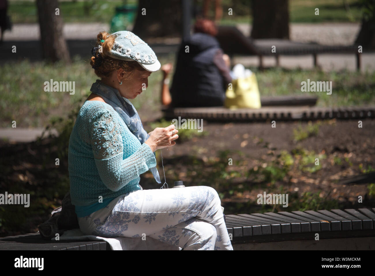 Kharkiv, Ukraine - June 30, 2019: An adult woman in a beautiful handmade sweater and cap sits on a bench in a city park and crochets a new product. - Stock Image