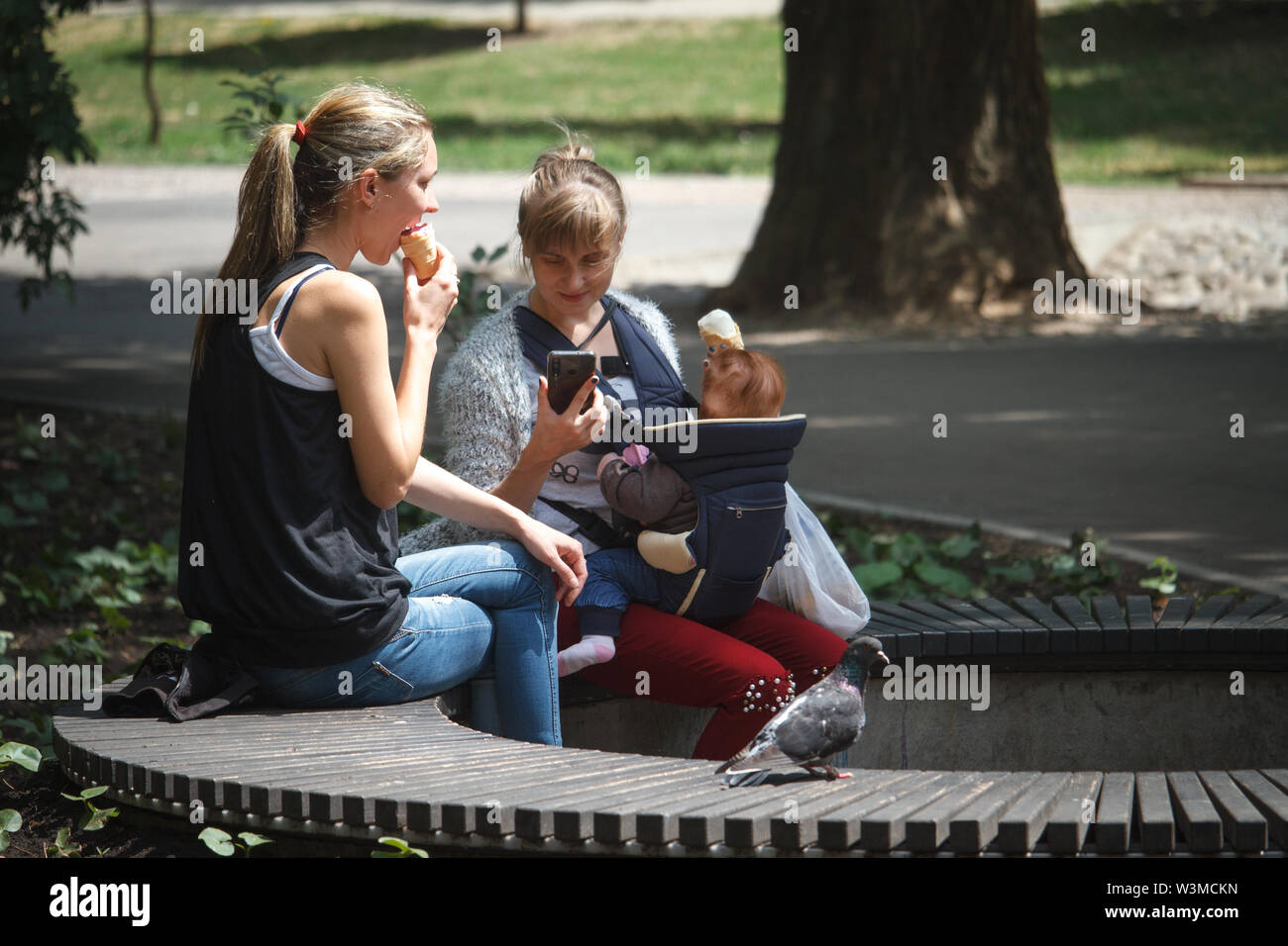 Kharkiv, Ukraine - June 30, 2019: A young mother with a baby in a backpack and a friend are relaxing on a bench in a city park - Stock Image