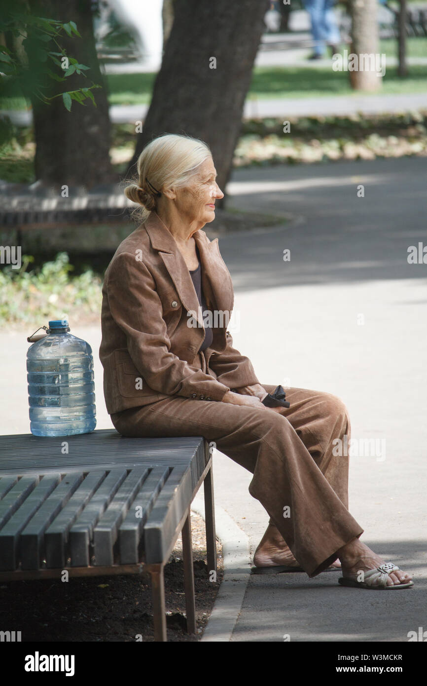 Kharkiv, Ukraine - June 30, 2019: Elderly woman in elegant clothes sit on a bench in the city park and next to a large bottle of water from the spring - Stock Image