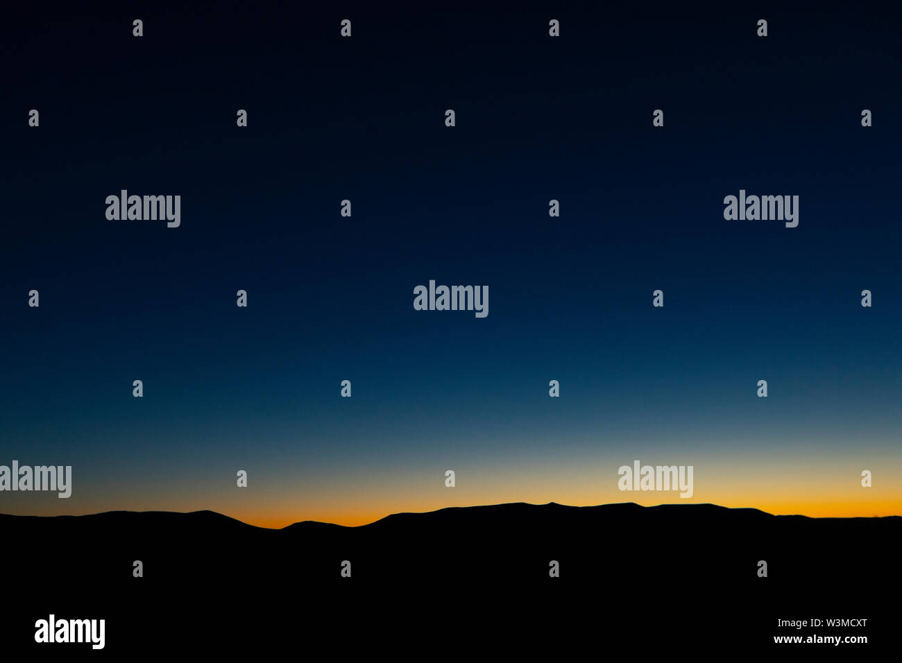 Silhouette of mountains at sunset - Stock Image