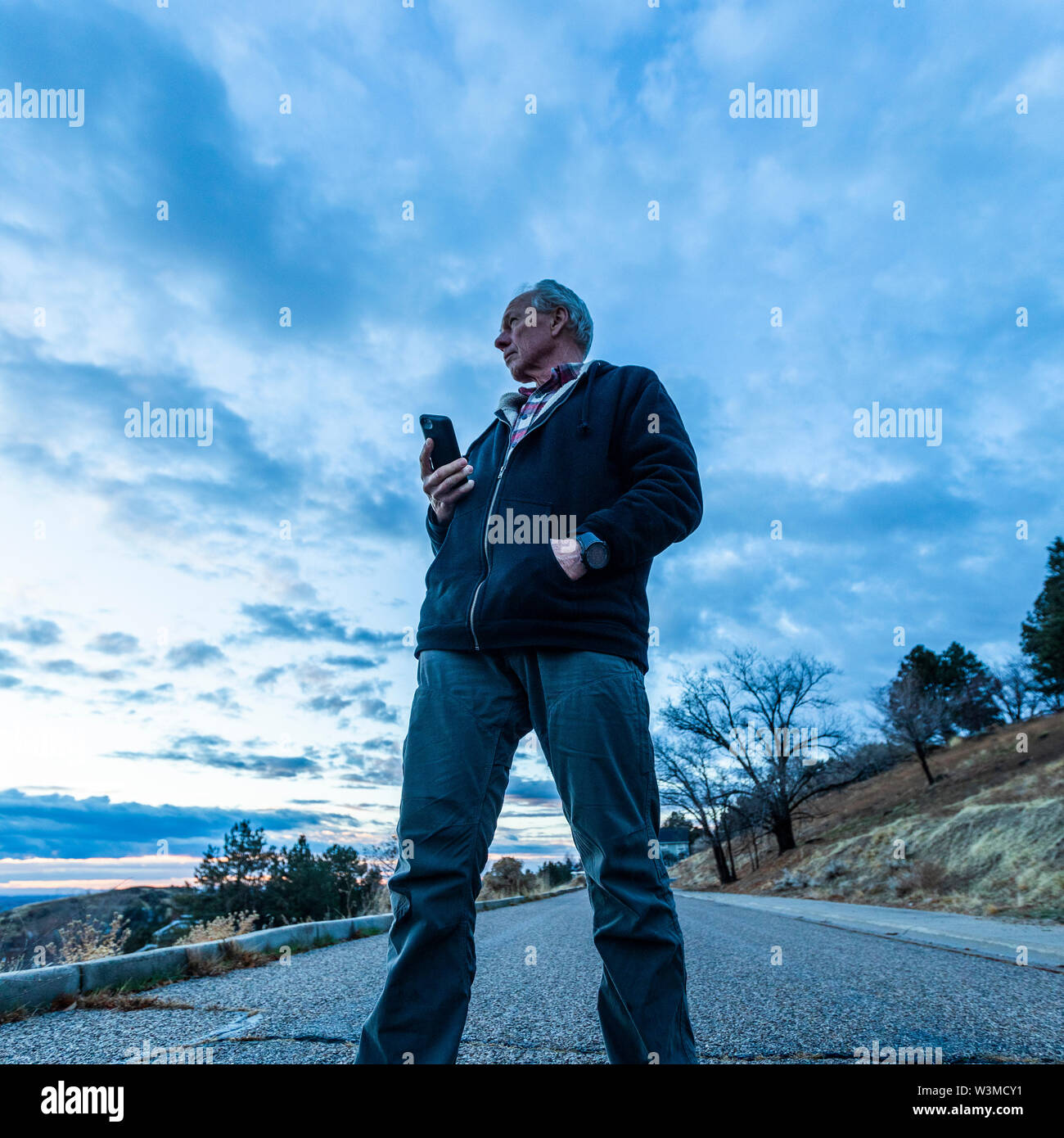 Low angle view of man holding smart phone on road - Stock Image