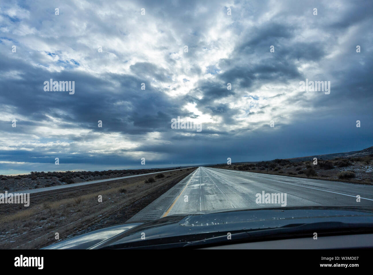 Car on country road under overcast sky - Stock Image