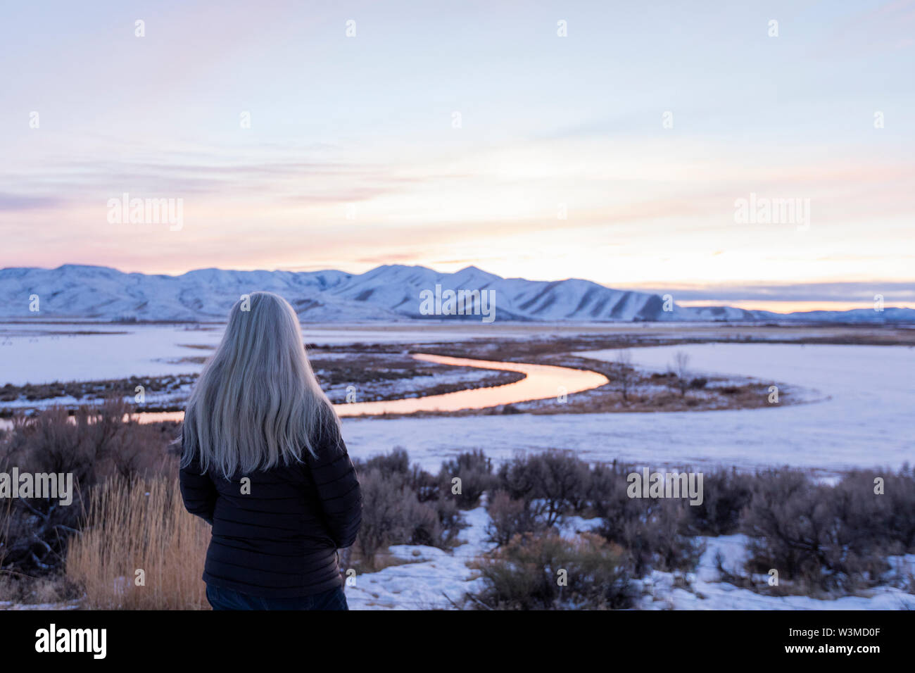 Mature woman by river during winter in Picabo, Idaho - Stock Image