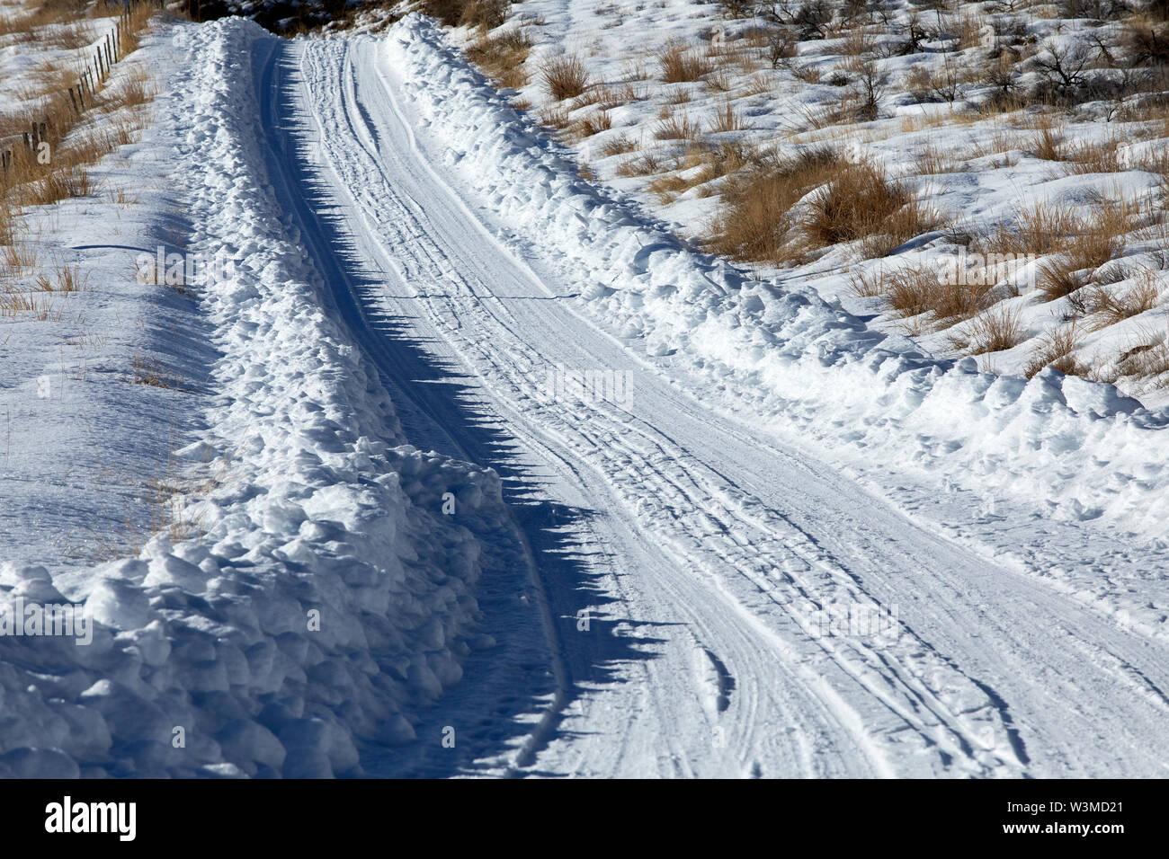 Tire tracks through snow - Stock Image
