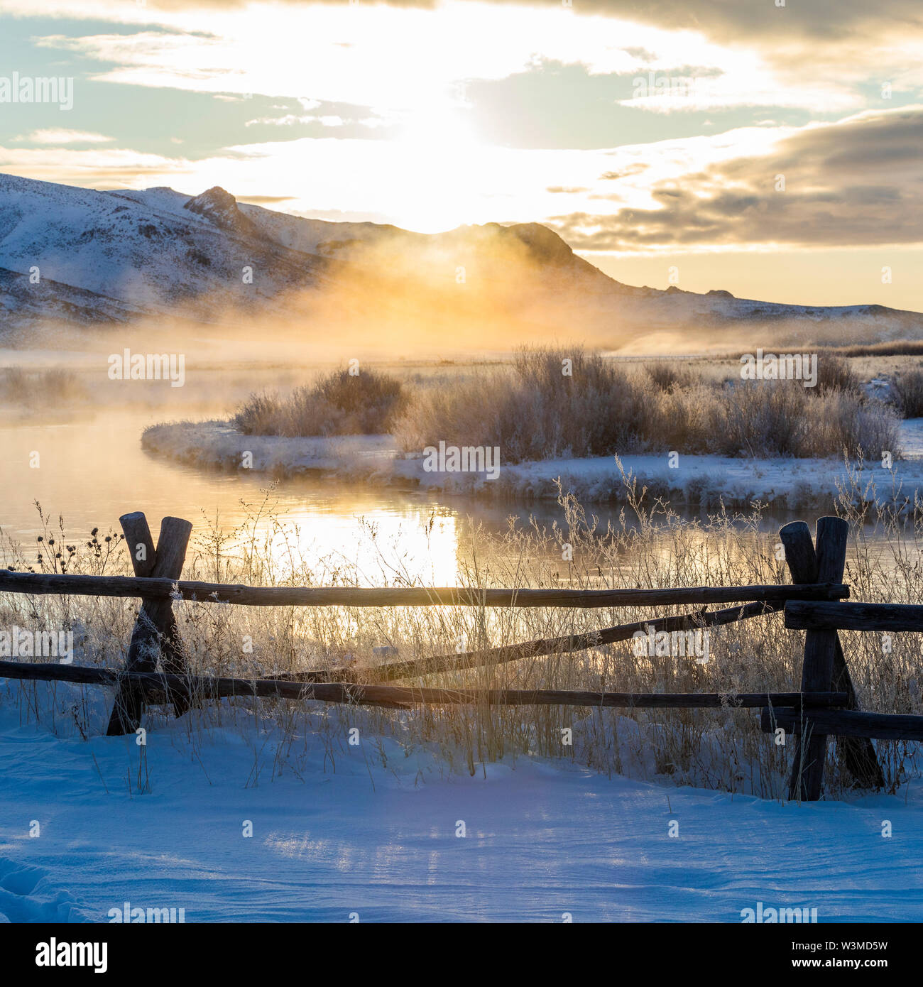 Fence by river at sunrise in Picabo, Idaho - Stock Image