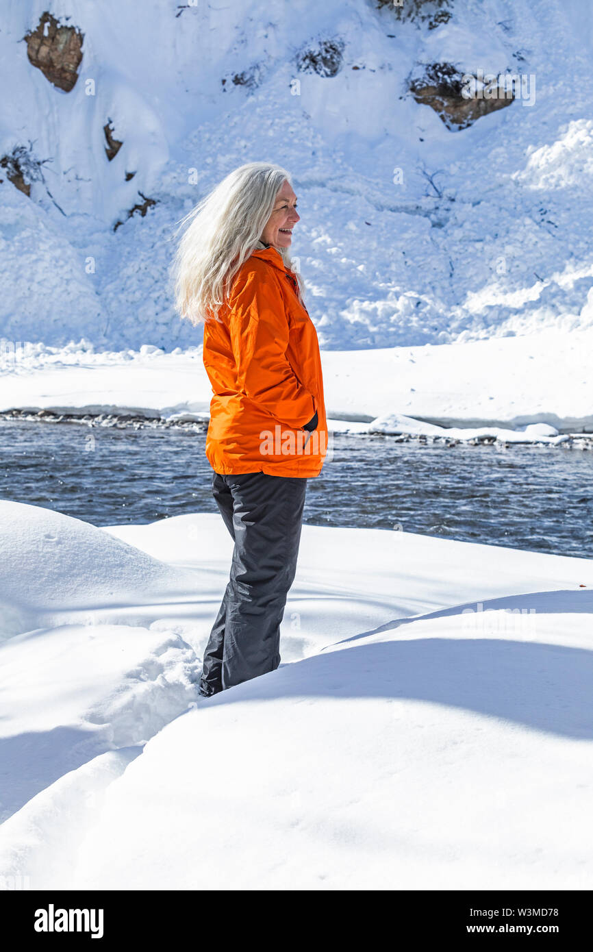 Mature woman wearing orange coat on snow by river - Stock Image
