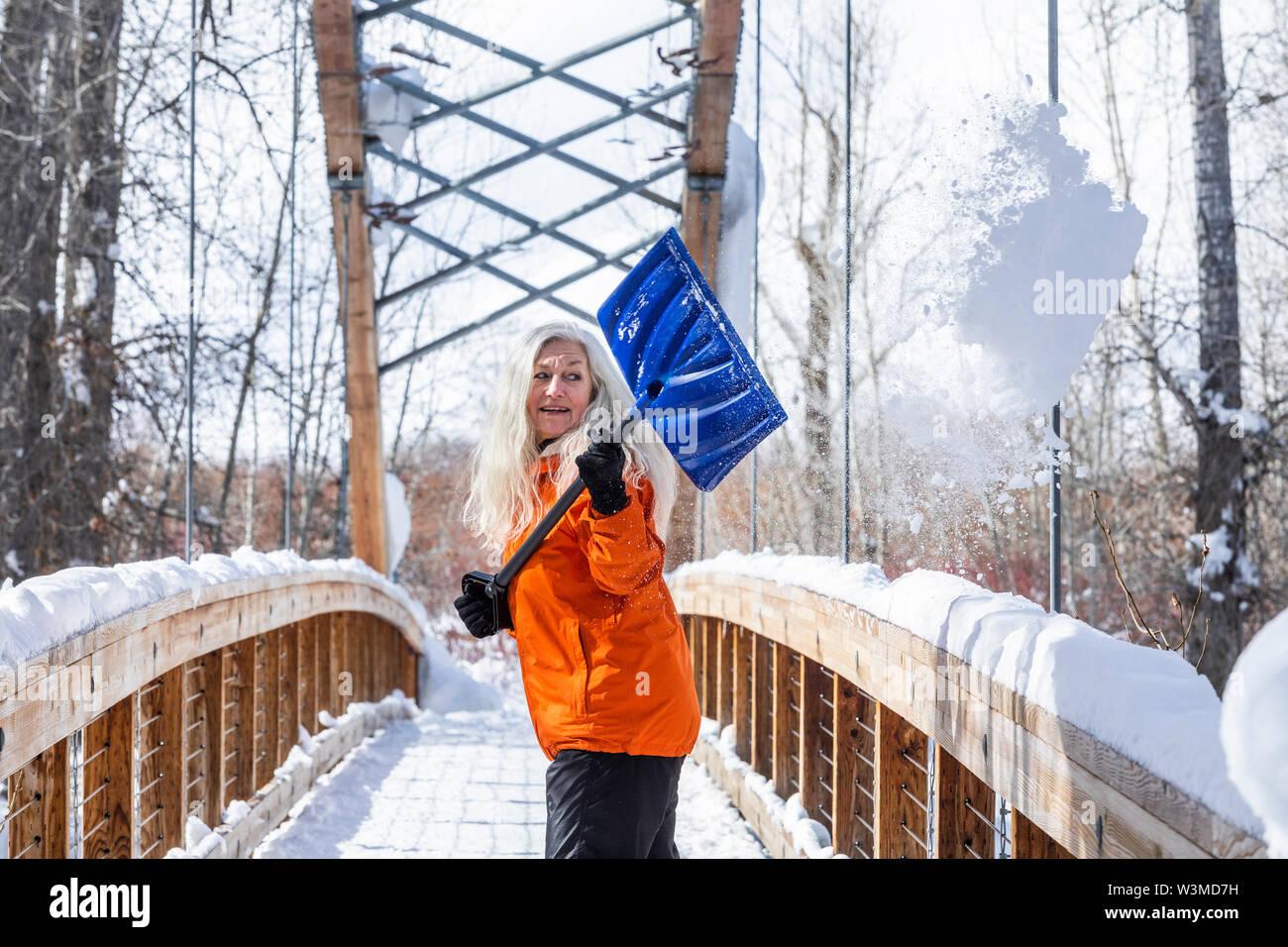 Mature woman shoveling snow off of footbridge - Stock Image