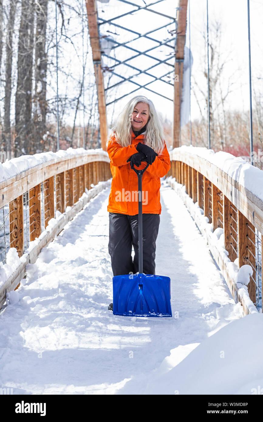Mature woman holding shovel on snow covered footbridge - Stock Image