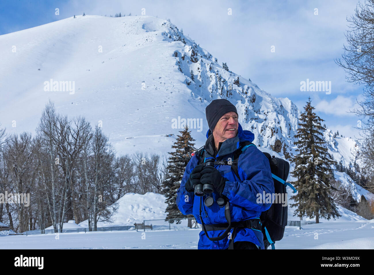 Senior man holding binoculars by snow covered mountain in Sun Valley, Idaho, USA - Stock Image