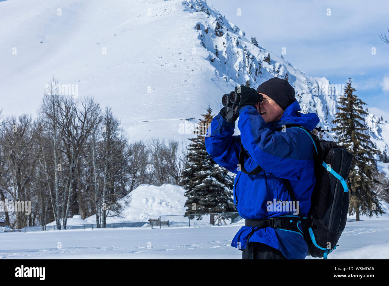 Senior man using binoculars by snow covered mountain in Sun Valley, Idaho, USA - Stock Image
