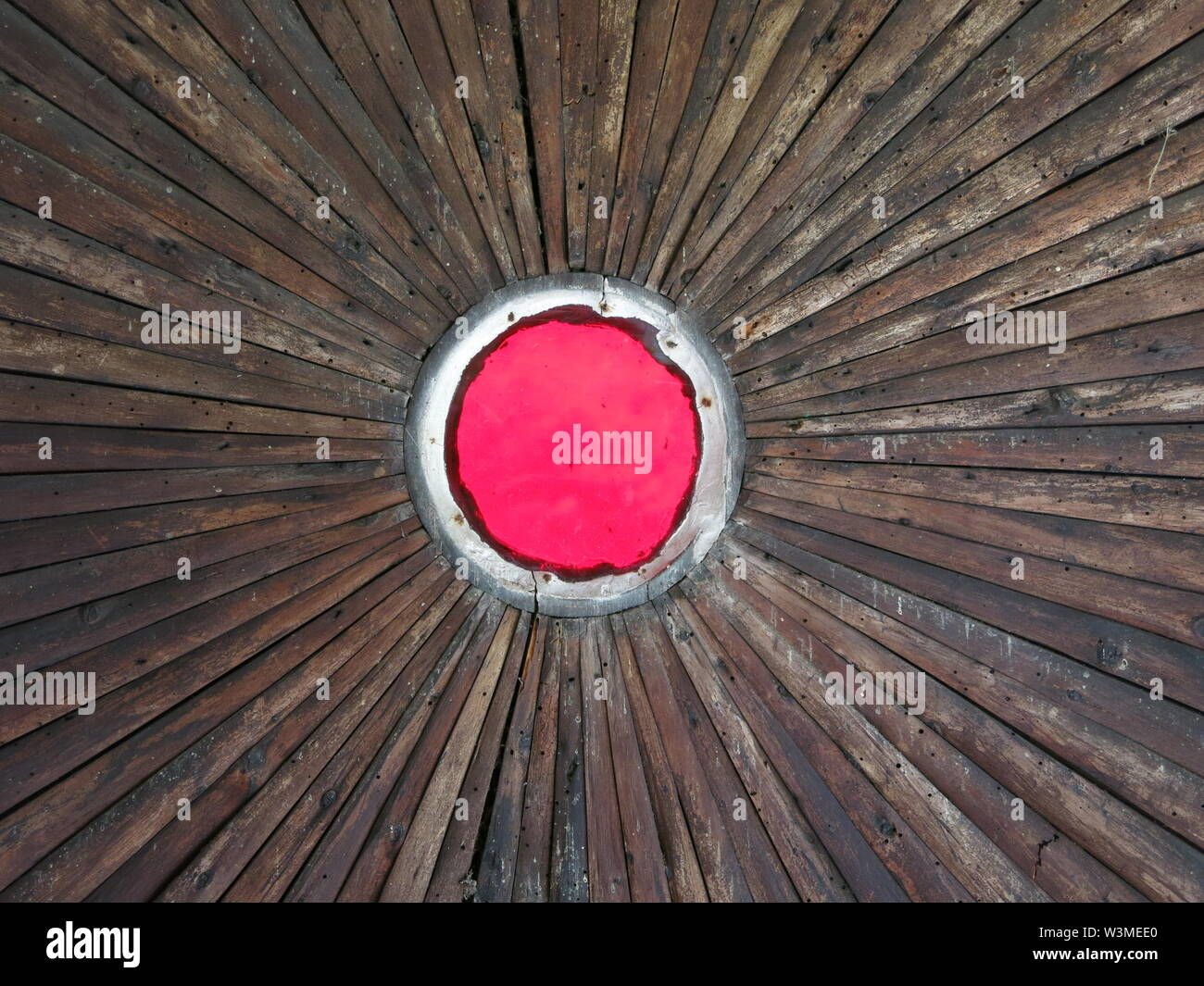 Bull's Eye: abstract image of a red circle with a white circumference, surrounded by wooden spokes radiating like the sun - Stock Image