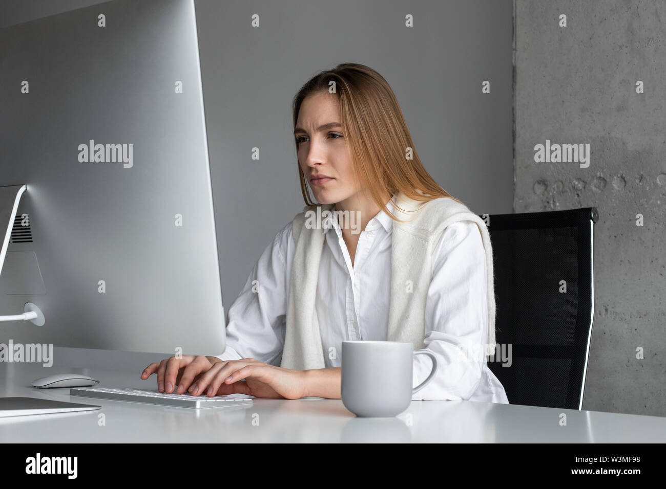 Businesswoman concentrating while working at computer - Stock Image