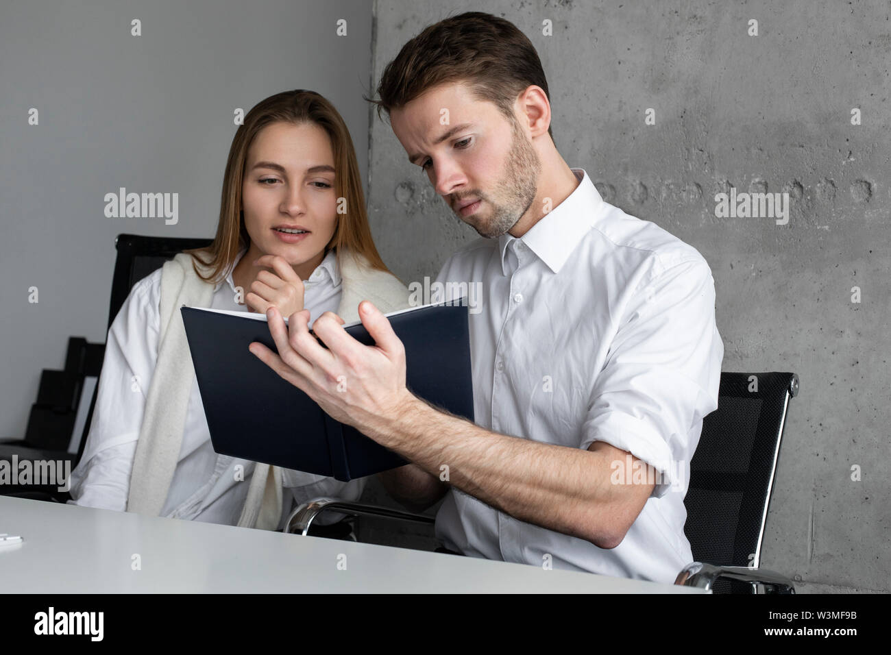 Businessman showing notebook to colleague - Stock Image