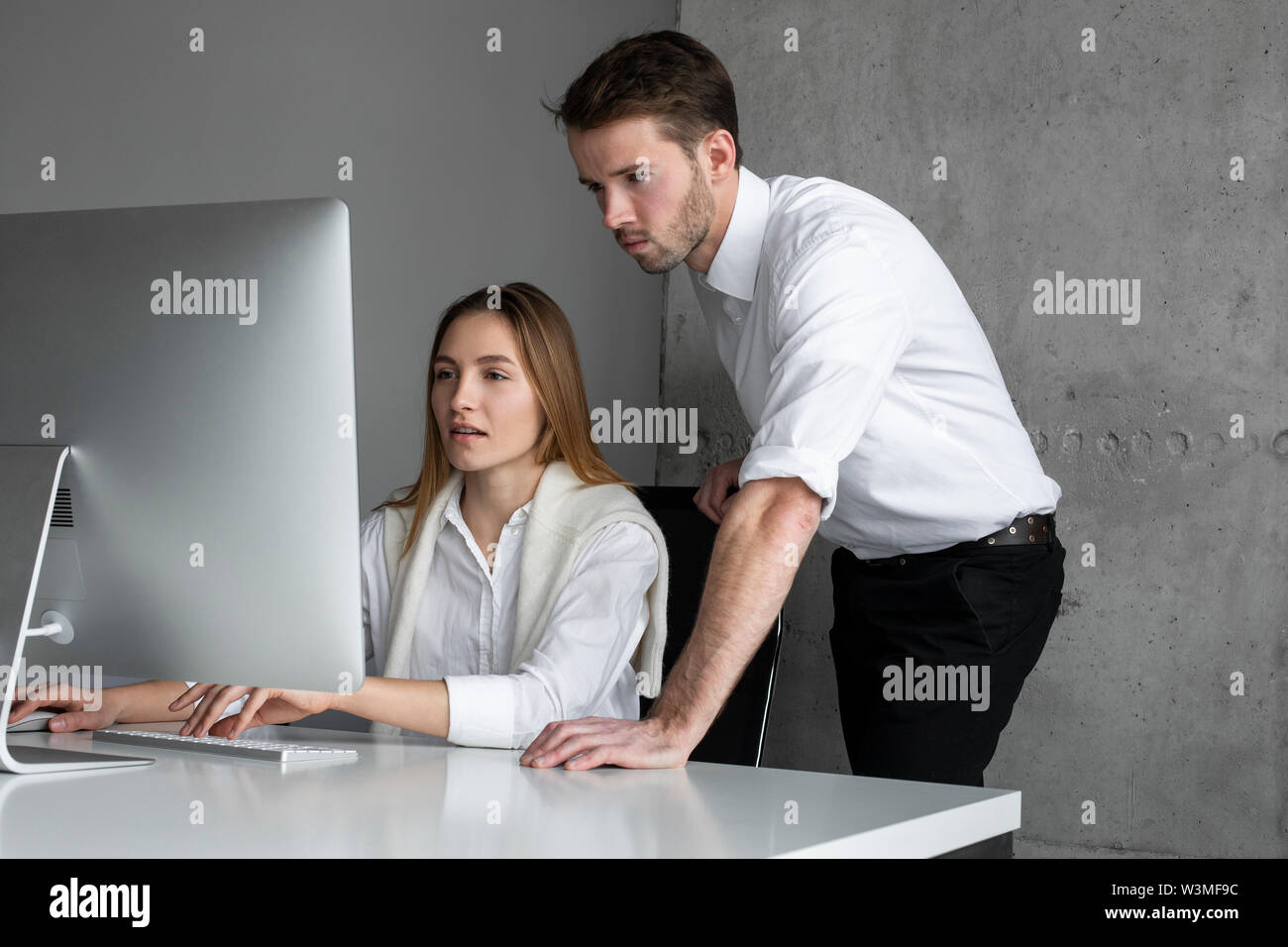 Businesspeople using computer together - Stock Image