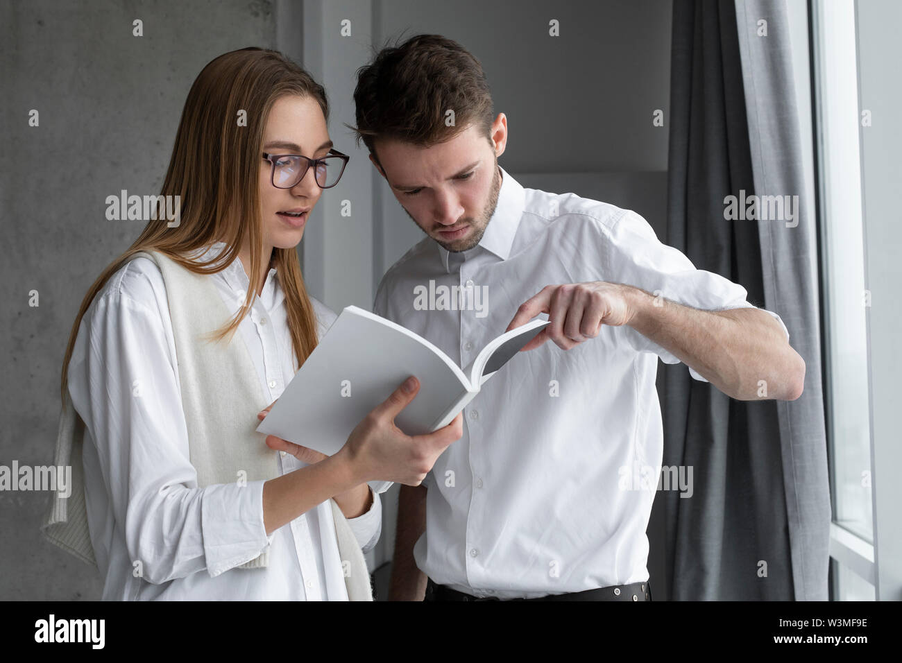 Businessman pointing to page in book for colleague - Stock Image
