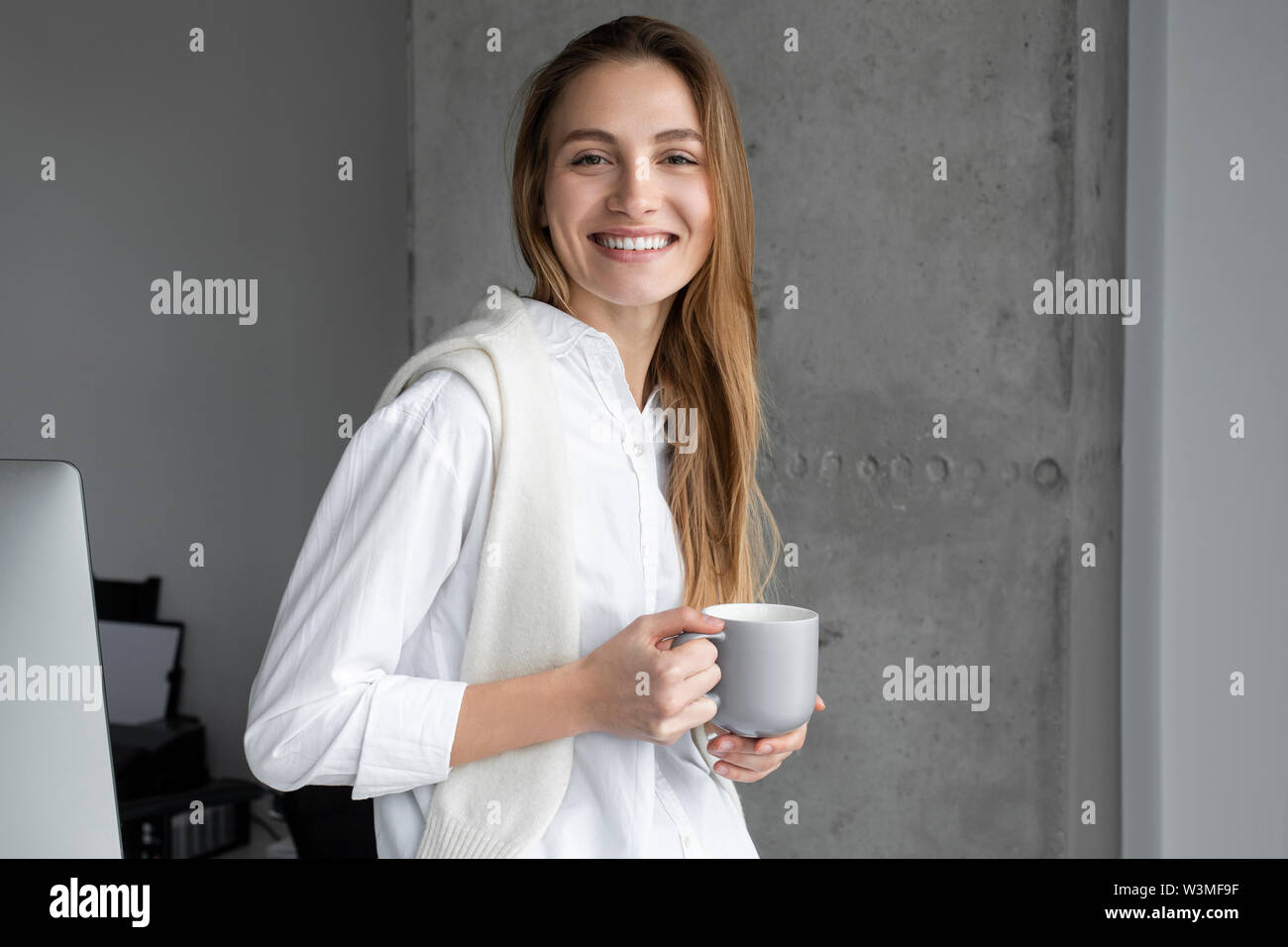 Smiling businesswoman with coffee cup - Stock Image