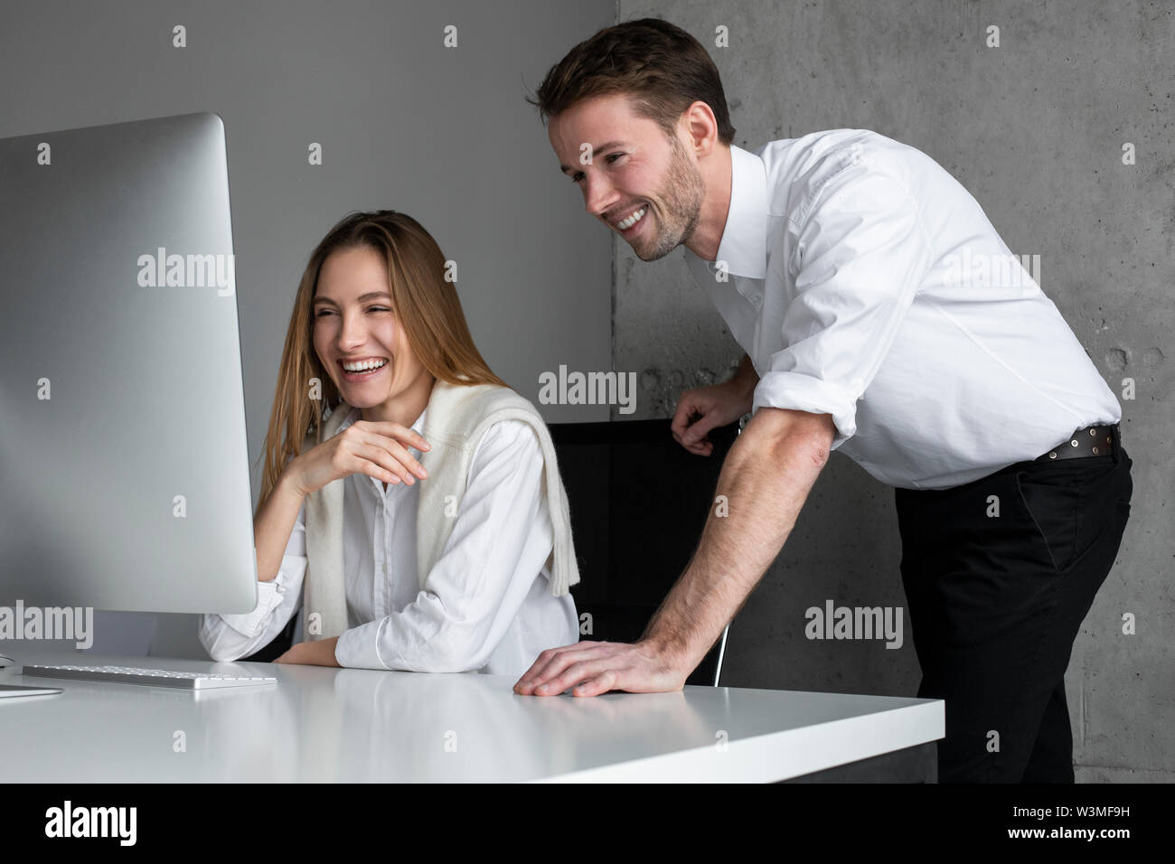 Smiling businesspeople using computer - Stock Image