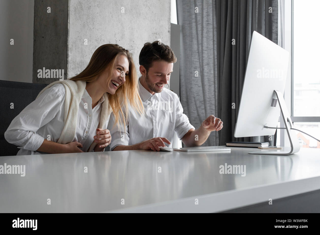 Colleagues laughing at desk - Stock Image