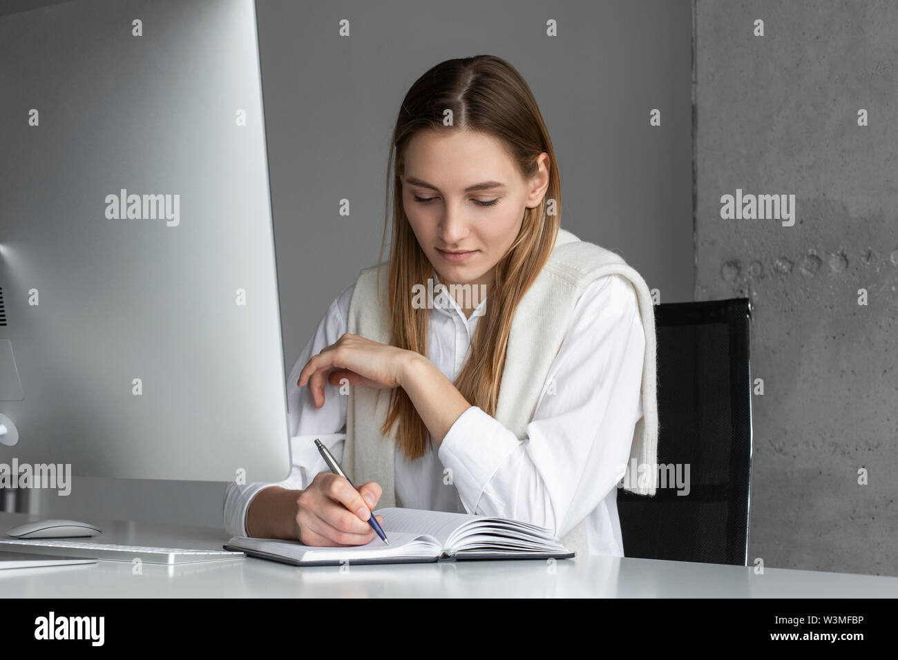 Businesswoman writing in notebook - Stock Image