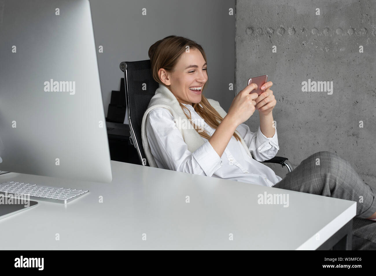 Laughing businesswoman using smartphone at desk - Stock Image