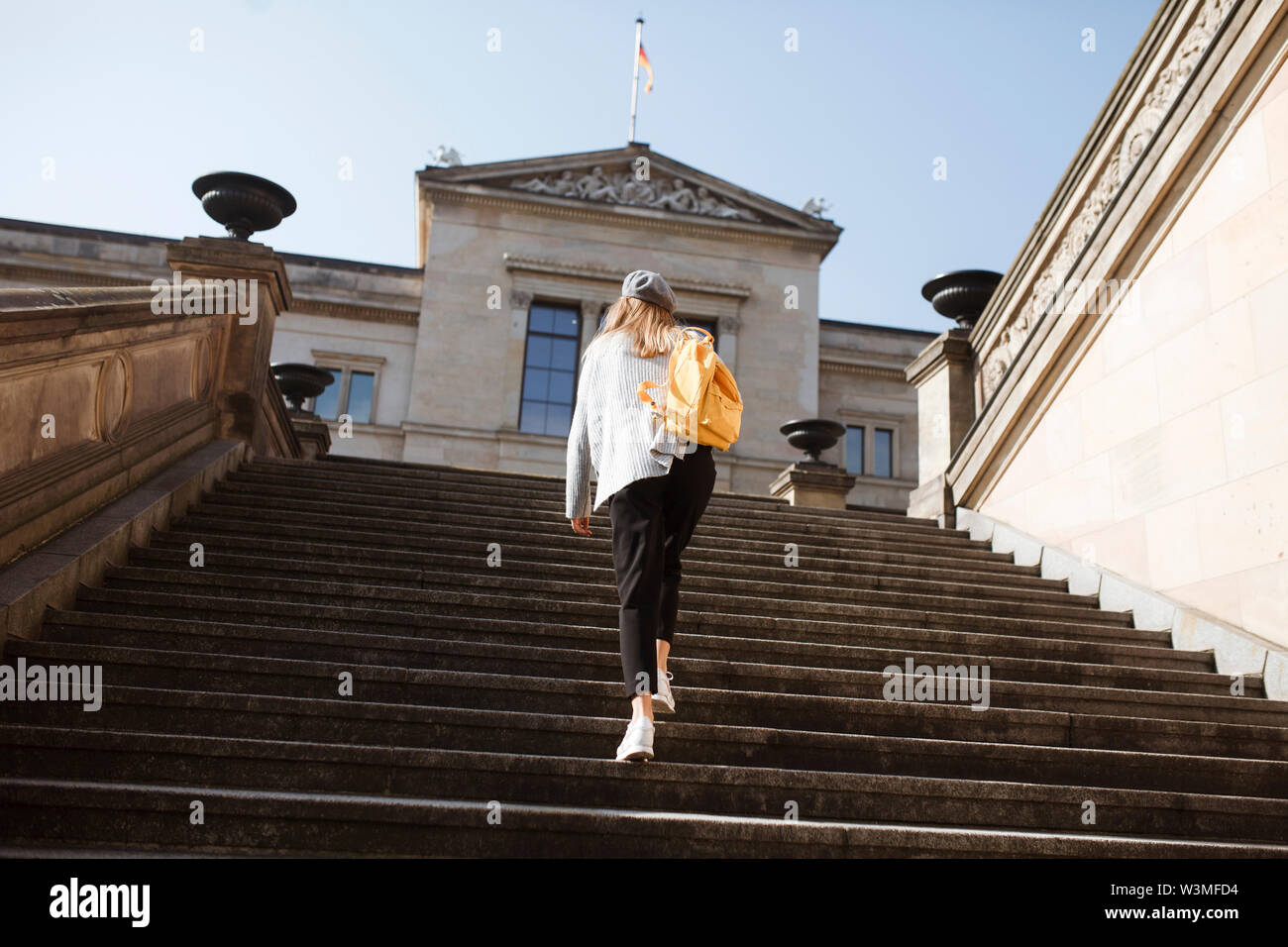 Young woman walking on steps in Berlin, Germany - Stock Image