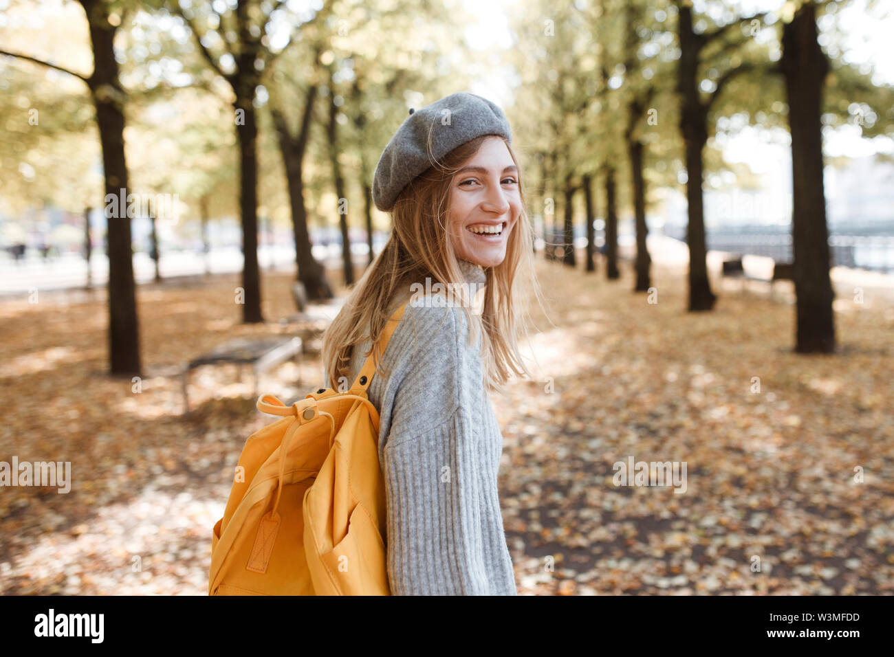 Young woman with yellow backpack in park in Berlin, Germany - Stock Image