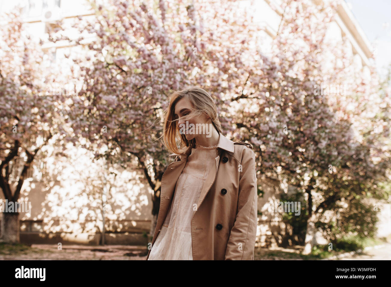 Smiling young woman by blossoming trees - Stock Image