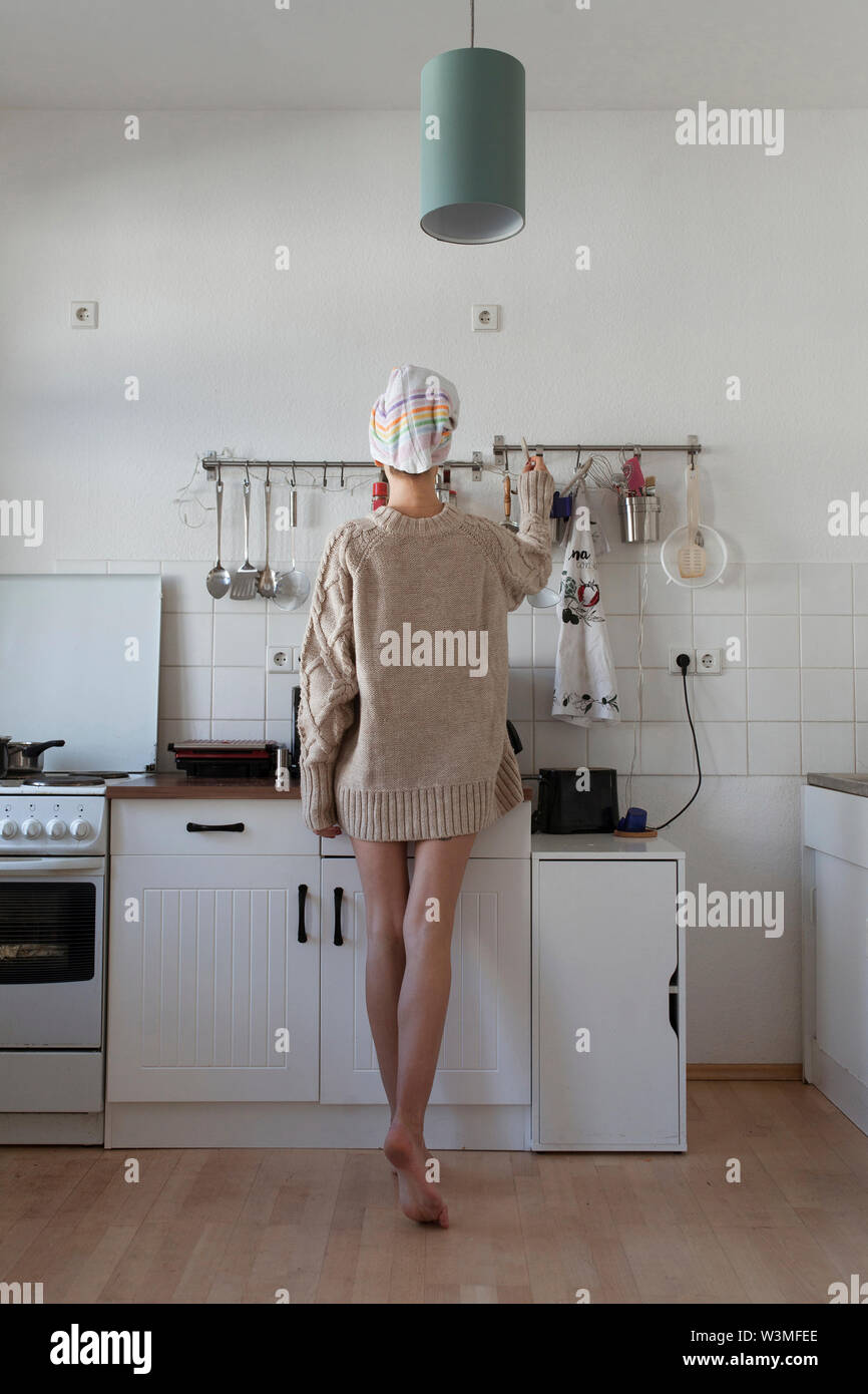 Rear view of young woman in apartment kitchen - Stock Image